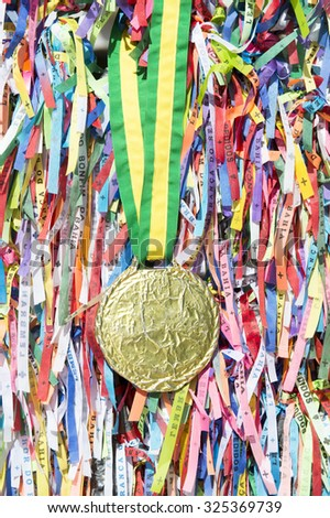 Gold medal hanging on a colorful wall of Brazilian wish ribbons for good luck