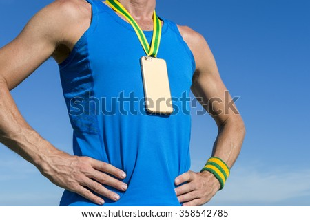Gold medal in the shape of mobile phone hanging from a green and yellow ribbon on the chest of an athlete against blue sky - stock photo