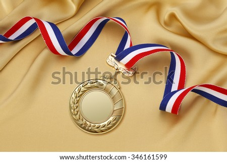 Gold medal on a gold satin background  - stock photo