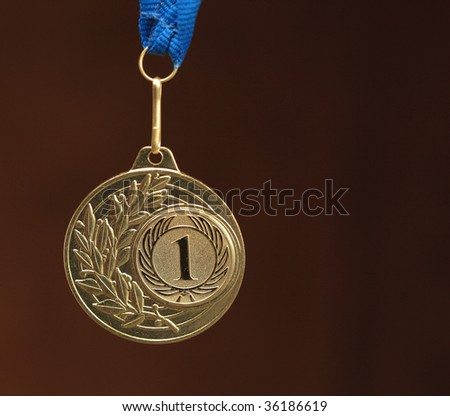 gold medal on brown background - stock photo