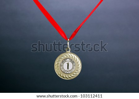 Gold medal on grey background - stock photo
