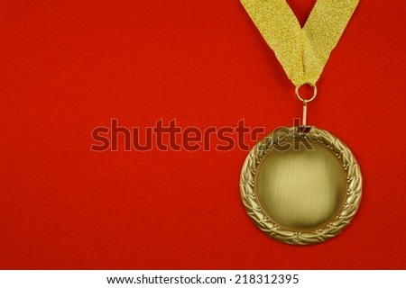Gold medal with golden ribbon on red velveteen with room for text