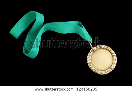 Gold medal with green ribbon isolated on black - stock photo