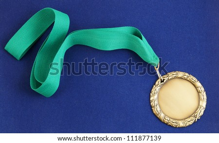 Gold medal with green ribbon on blue velveteen - stock photo