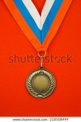 Gold medal with ribbon on red velveteen