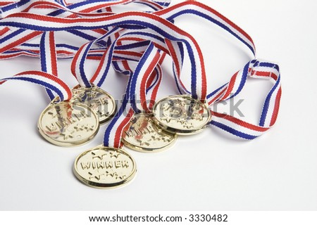 Gold medals shot against a white background symbolizing success - stock photo