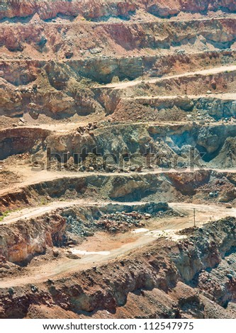 Gold mine open caste. Industrial landscape - stone textured of the rock on the open pit - stock photo