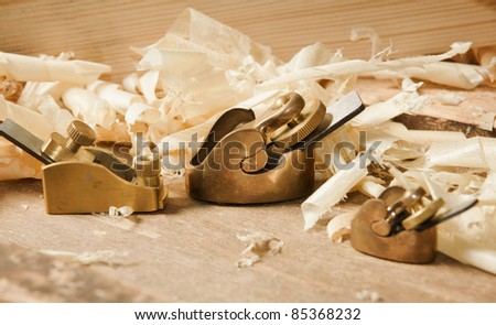 Gold miniature wood planer on wooden plank (Selective Focus, Focus on the central plane) - stock photo