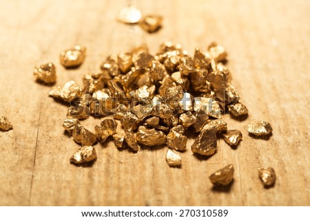 Gold. Mound of gold on a old wooden work table - stock photo