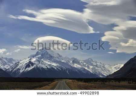 Gold-mounted road with Mount Cook rimmed with puffs of white cloud - stock photo