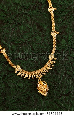Gold Necklaces on textured green background. - stock photo