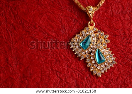 Gold Necklaces on textured red background. - stock photo