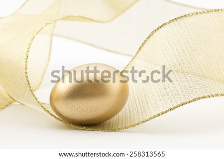 Gold nest egg placed in swirl of golden metallic ribbon creates sense of movement, excitement, and success.  - stock photo