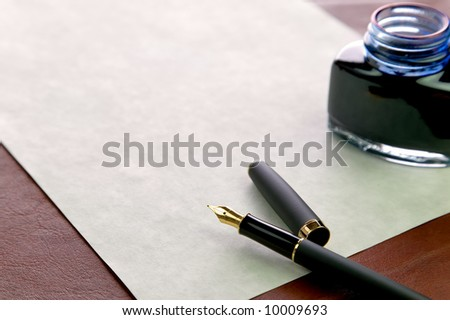 Gold nibbed fountain pen, watermarked expensive paper and an inkwell on a leather desk top, shallow DOF, focus on the nib. - stock photo