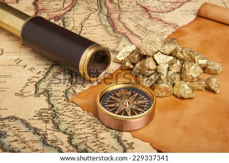 Gold nuggets and vintage brass telescope on antique map  - stock photo