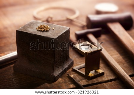 Gold nuggets on a old anvil, with tools in background. intentionally shot in nostalgic tone. Shallow depth of field. - stock photo