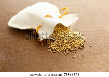 gold nuggets spilling out from a small pouch. - stock photo