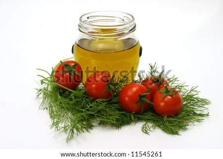gold olive oil in transparent little jar with cherry tomatoes and fennel
