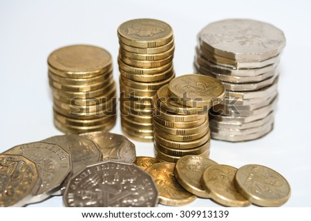 Gold one and two dollar coin and silver fifty cent pieces in columns and stacks with scattered coins isolated on white. - stock photo