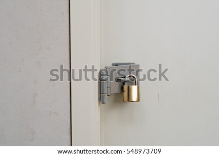Gold padlock at the white door