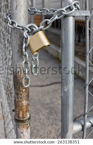 Gold Padlock with chain used on a chainlink fence. Selective focus is use on the padlock. - stock photo