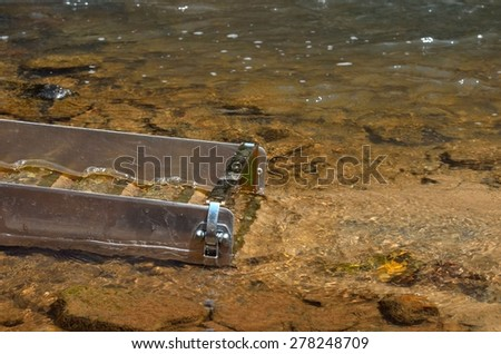 Gold panning in a river with a sluice box - stock photo