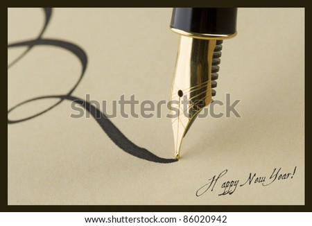 Gold pen on christmas postcard - stock photo