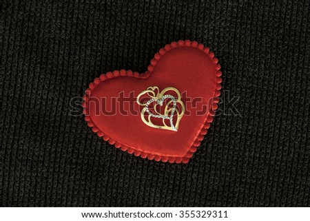 Gold pendant in the shape of hearts and red heart on a fabric basis.