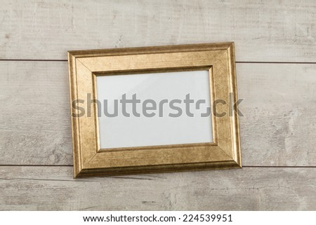Gold photo frame on wood table  - stock photo