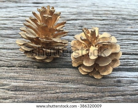 Gold pine cones on wooden background