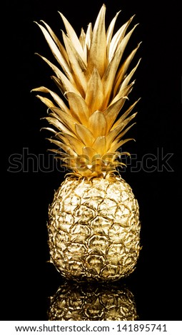 Gold pineapple on black background - stock photo