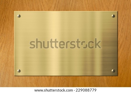 gold plaque on wood background - stock photo