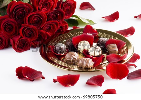 Gold plate of luxury chocolates with red roses - stock photo