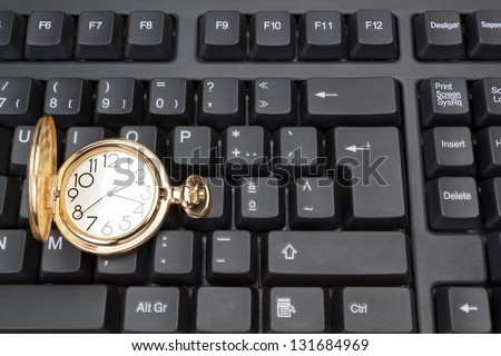 Gold pocket watch against the background of a computer keyboard.