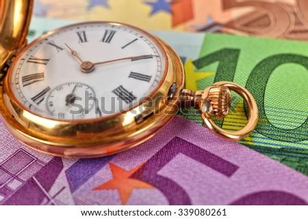 gold pocket watch and euro banknotes, close up - stock photo