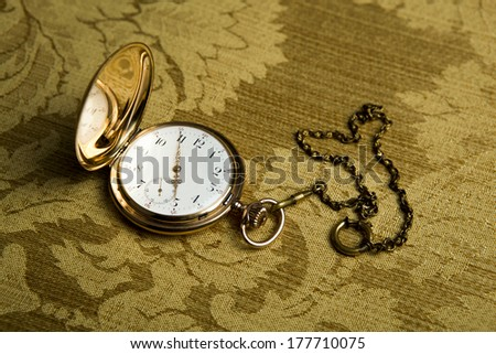 Gold pocket watch on on gold cloth close-up