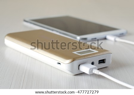 Gold power bank charges the tablet PC. Close-up