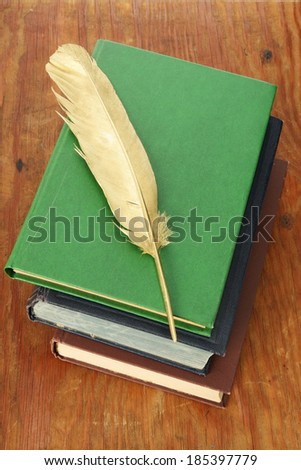 Gold quill pen and pile of books on grunge wood board - stock photo