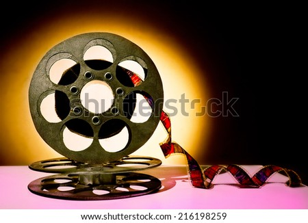 Gold reel of film on a black background - stock photo