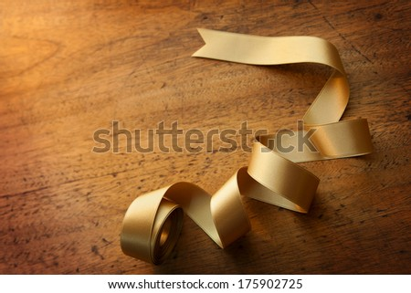 Gold ribbon nicely uncurled, on old wooden desk. Preparation for gift wrapping.  - stock photo