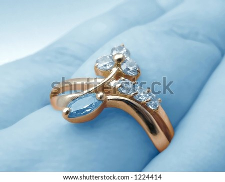 Gold ring on blue background - stock photo