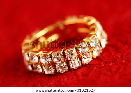 Gold ring on textured background - stock photo