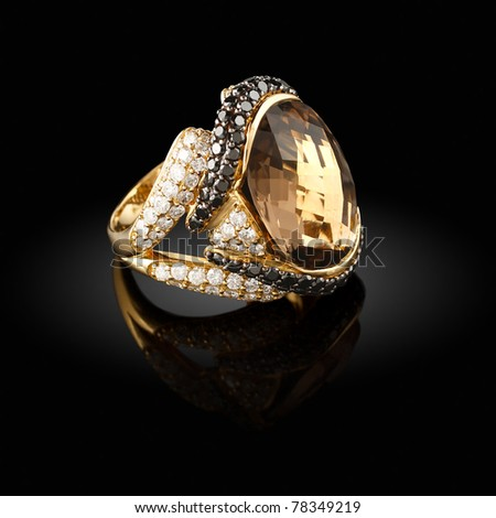 Gold ring with a brilliants on a black background - stock photo