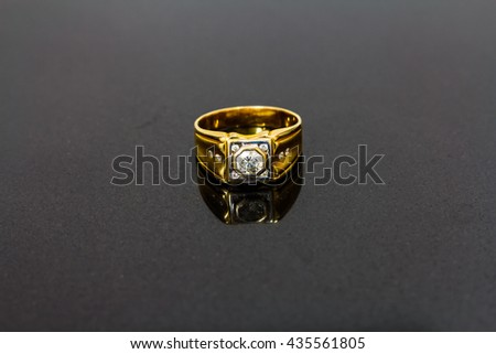 Gold ring with diamond on black background, selective focus - stock photo