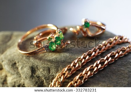 Gold ring with emerald near chain on gray stone against nice dark background - stock photo