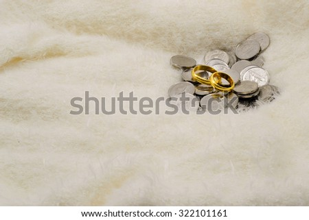 gold rings and coins on furry fabric - stock photo