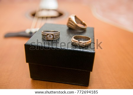 Gold rings, case and acoustic guitar in the background