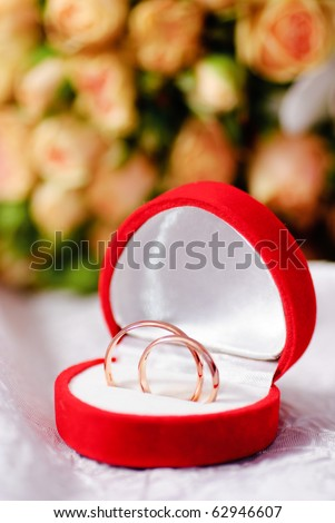 Gold rings on background of a bouquet of roses. Shallow DOF, selective focus