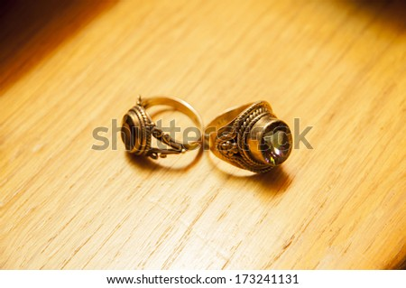 gold rings with gems on a wooden background - stock photo