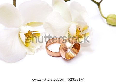 Gold rings with white orchid isolated on white background - stock photo